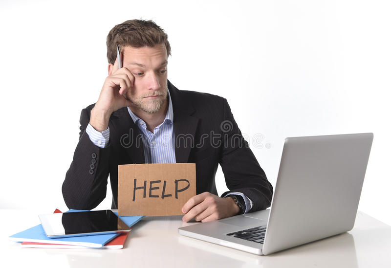Attractive businessman working in stress at computer holding help cardboard sign royalty free stock image