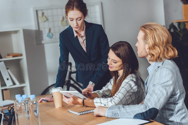 attractive businesspeople looking at tablet stock photography
