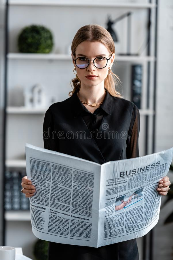 Attractive businesswoman in black clothes and glasses holding newspaper and looking. At camera stock photos