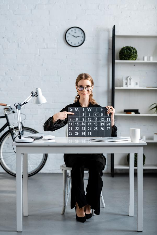 Attractive businesswoman in black clothes and glasses. Showing calendar royalty free stock images