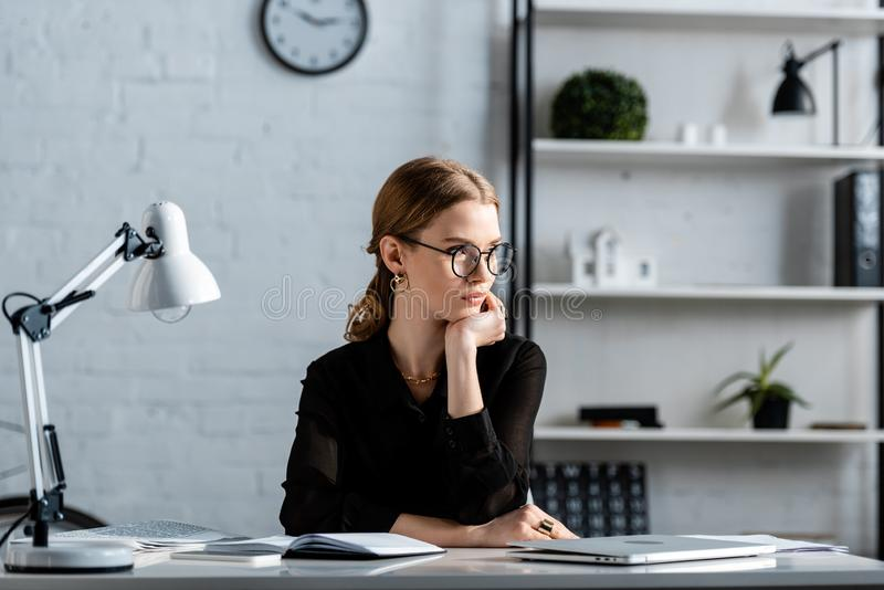 Attractive businesswoman in black clothes and glasses sitting on chair and. Touching face royalty free stock photography