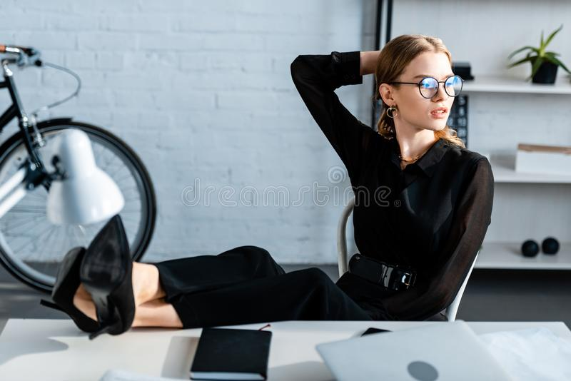 Attractive businesswoman in black clothes and shoes sitting at office and. Touching head royalty free stock photo