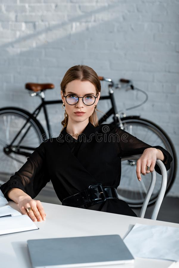 Attractive businesswoman in black clothes sitting on chair and looking. At camera royalty free stock photography
