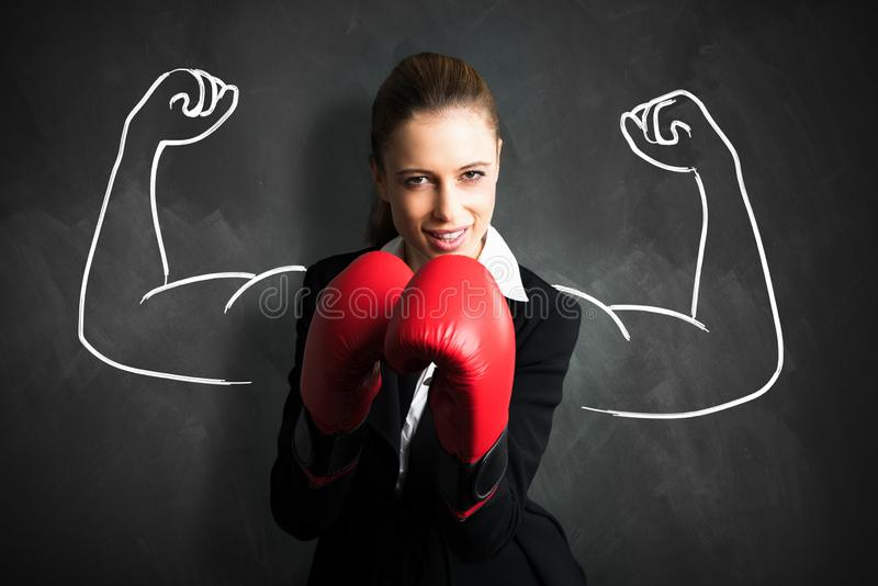 Attractive businesswoman with boxing gloves ready for a fight. In front of a blackboard with drawn muscular arms stock photo