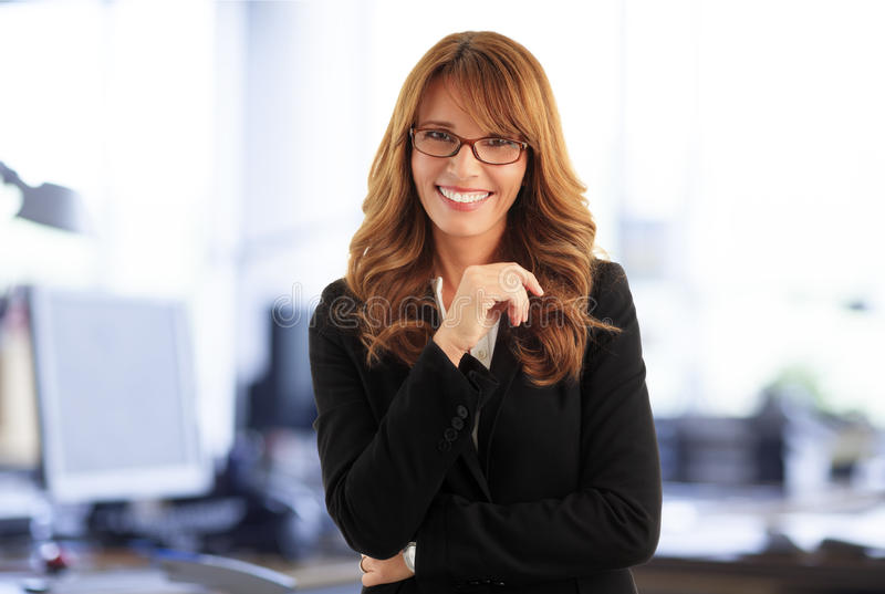 Attractive businesswoman. Close- up portrait of attractive middle age businesswoman standing at office while looking at camera and smiling royalty free stock images