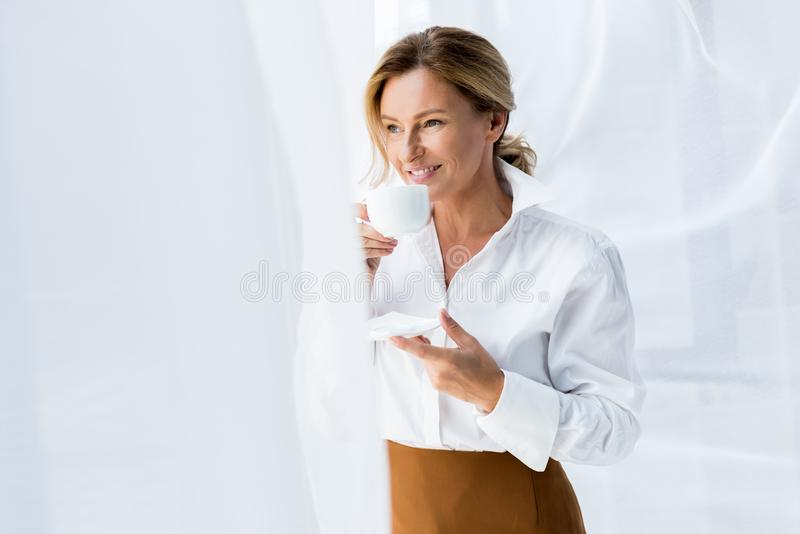 Attractive businesswoman drinking coffee and looking at window. In office royalty free stock photo