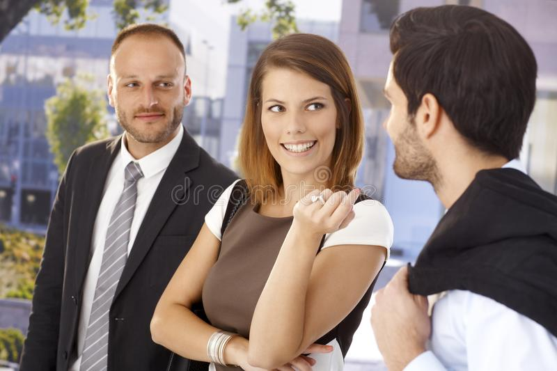 Attractive businesswoman flirting with colleague. In front of office center, outdoors. Suit and tie, ring stock photos