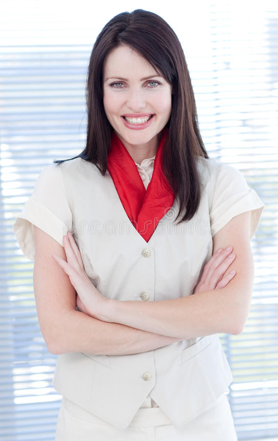 Attractive businesswoman with folded arms smiling. At the camera stock image