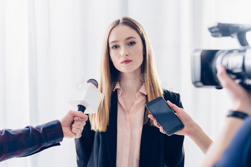 Attractive businesswoman giving interview to journalists. In office stock photos