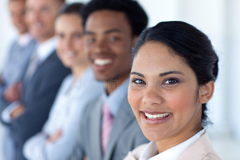 Attractive businesswoman with her team in a row. Attractivel businesswoman with her team in a row smiling at the camera royalty free stock photo