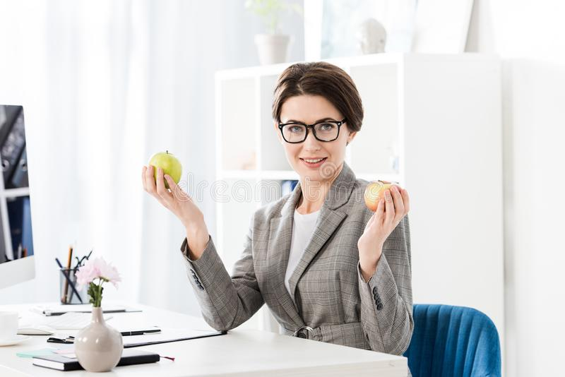 Attractive businesswoman holding apples and looking at camera. In office stock images