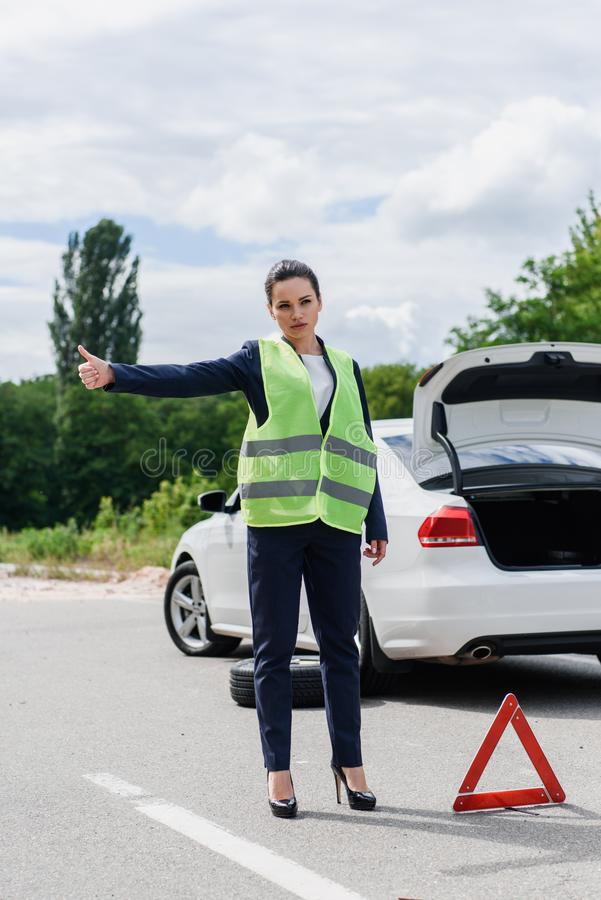 attractive businesswoman in light green vest hitchhiking on road royalty free illustration