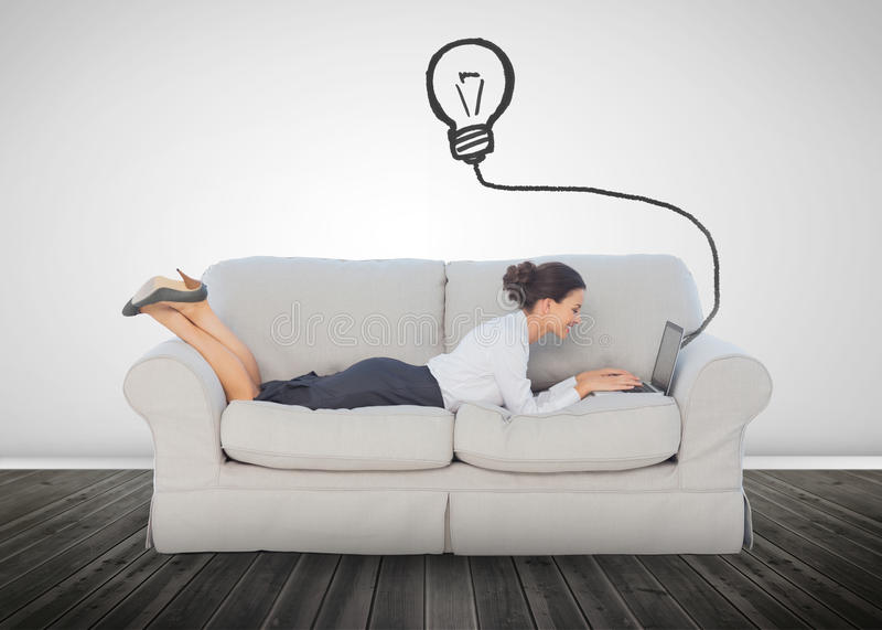 Attractive businesswoman lying on a couch and typing on her laptop. With a light bulb above her head stock images