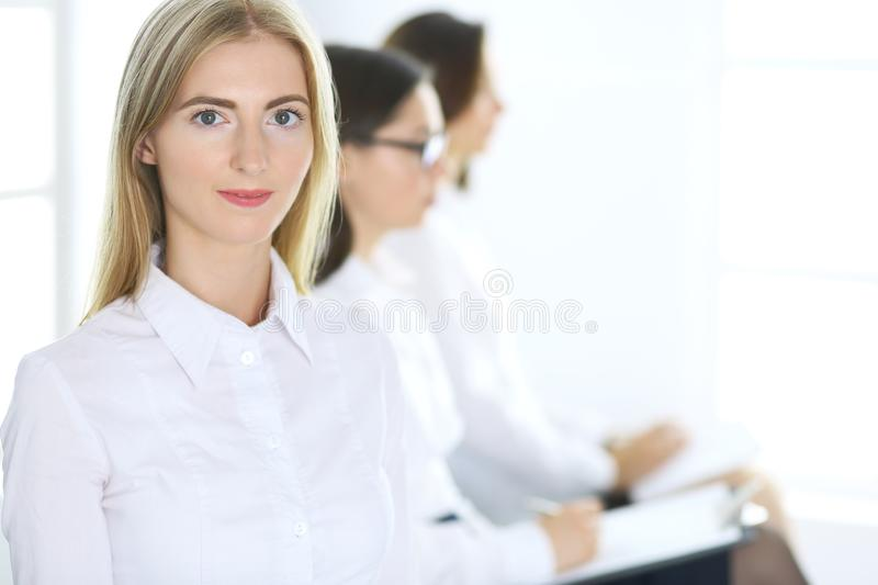 Attractive businesswoman at meeting or conference against the background of colleagues. Group of business people at work royalty free stock photography