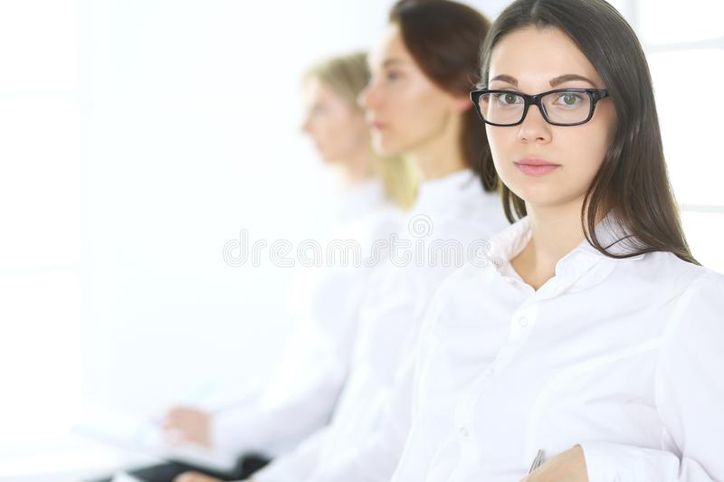 Attractive businesswoman at meeting or conference against the background of colleagues. Group of business people at work. Portrait of lawyer or secretary royalty free stock photography