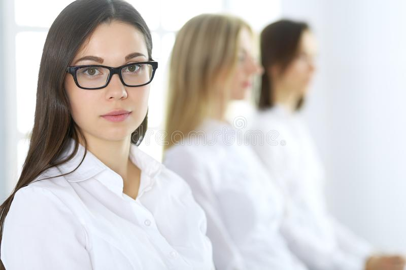 Attractive businesswoman at meeting or conference against the background of colleagues. Group of business people at work. Portrait of lawyer or secretary stock image