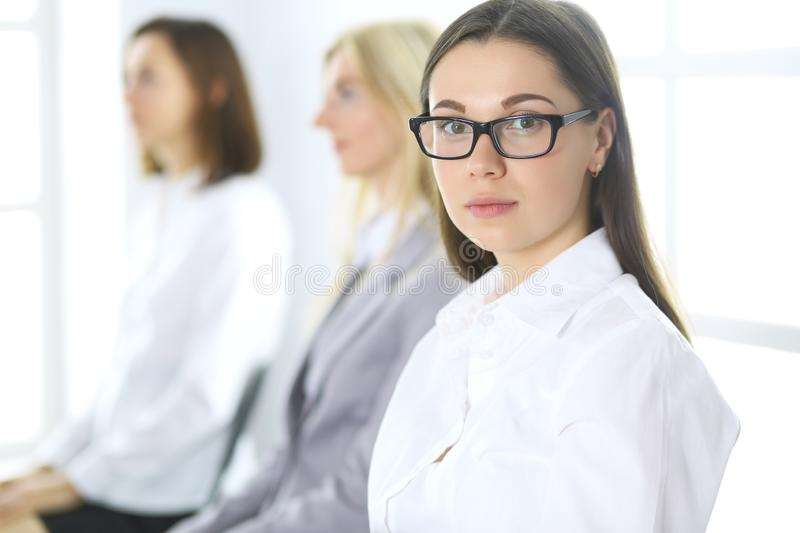 Attractive businesswoman at meeting or conference against the background of colleagues. Group of business people at work. Portrait of lawyer or secretary royalty free stock photos