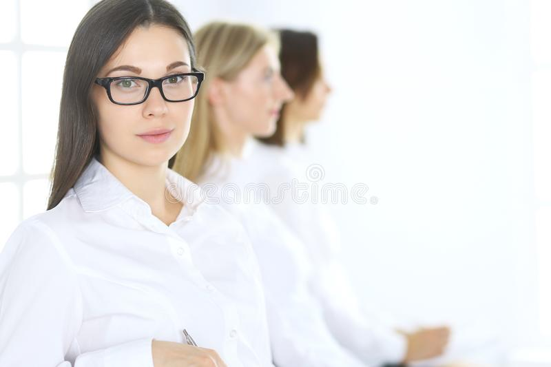 Attractive businesswoman at meeting or conference against the background of colleagues. Group of business people at work. Portrait of lawyer or secretary royalty free stock photo