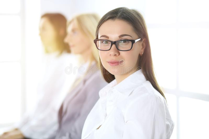 Attractive businesswoman at meeting or conference against the background of colleagues. Group of business people at work. Portrait of lawyer or secretary stock photos