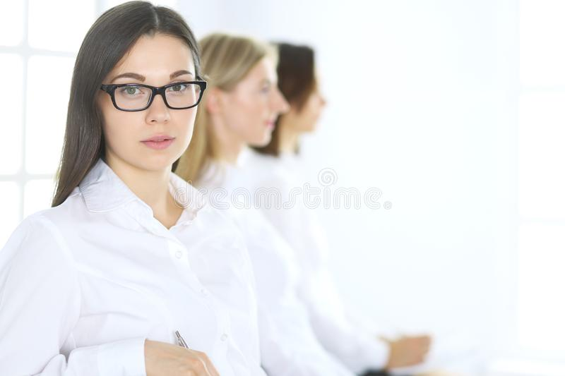 Attractive businesswoman at meeting or conference against the background of colleagues. Group of business people at work. Portrait of lawyer or secretary royalty free stock images