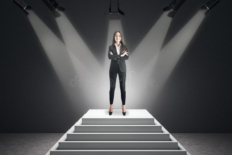Attractive businesswoman on pedestal. Best employee and leadership concept. Attractive businesswoman standing on illuminated pedestal on concrete background stock photography