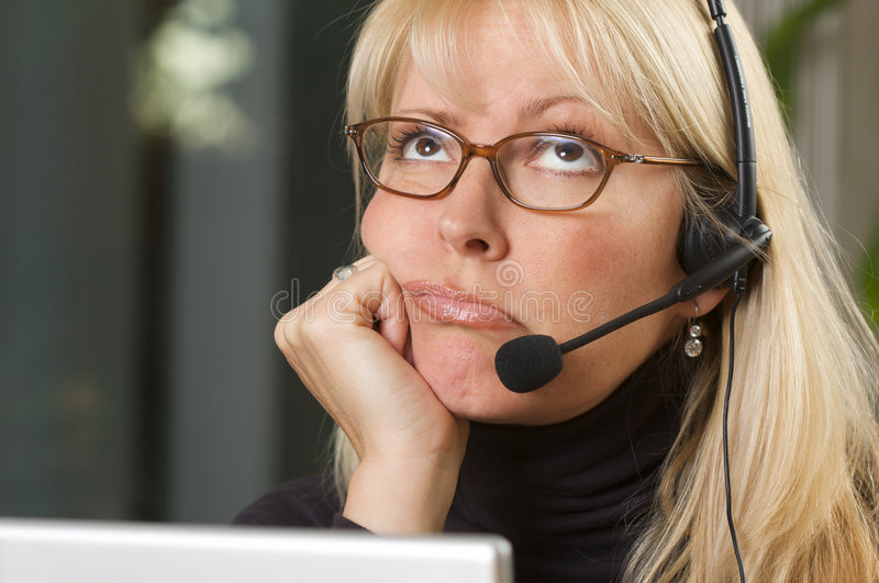 Attractive Businesswoman with Phone Headset. Attractive businesswoman shows signs of boredom & frustration while on her phone headset stock photo
