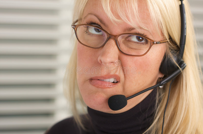 Attractive Businesswoman with Phone Headset. Attractive businesswoman shows anger & frustration while talking on her phone headset royalty free stock photos