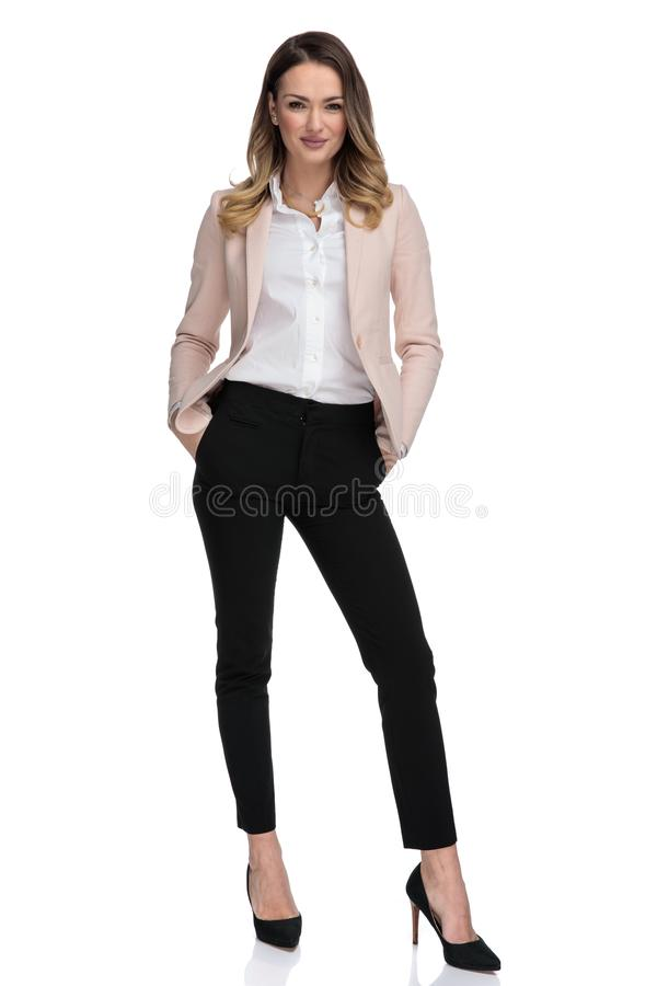 Attractive businesswoman in pink suit stands and hold pockets royalty free stock photo