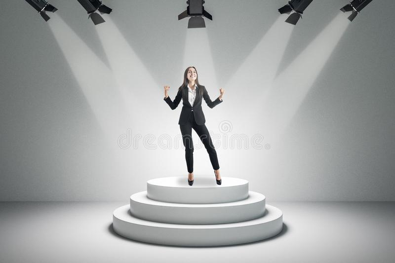 Attractive businesswoman on podium. Best employee and leadership concept. Attractive businesswoman standing on illuminated podium on concrete background royalty free stock photography