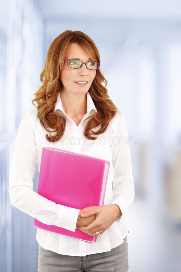 Attractive businesswoman. Portrait of middle age sales woman sitting at office and holding file in her hands royalty free stock photos