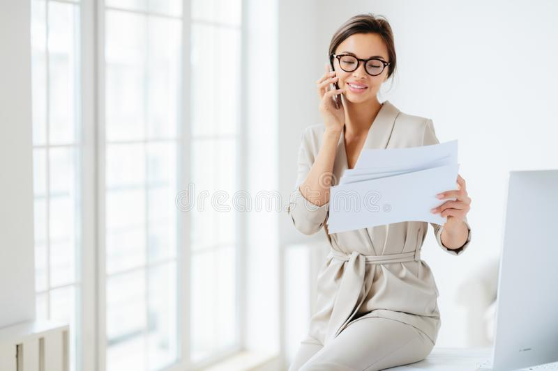 Attractive businesswoman reads papers or business documents, has telephone talk with business partner, examines paperwork before royalty free stock image
