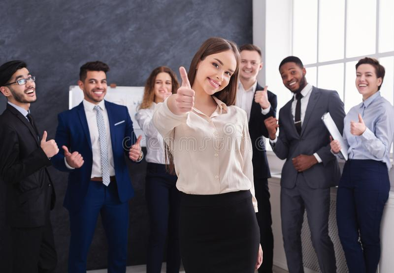 Attractive businesswoman showing thumb up in office stock images