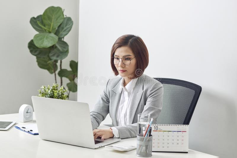 Attractive businesswoman is sitting at desk with computer and calendar in the office royalty free stock photos
