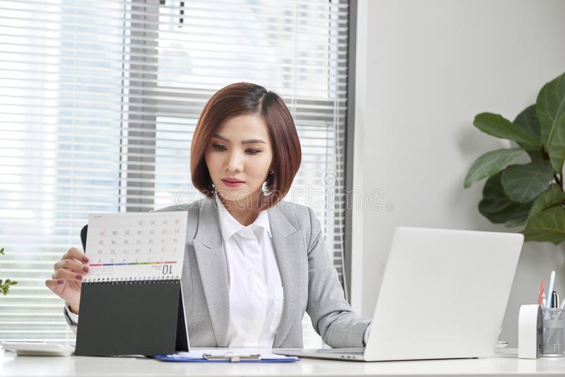 Attractive businesswoman is sitting at desk with computer and calendar in the office stock photos