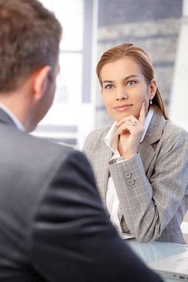 Attractive businesswoman sitting in office royalty free stock photos