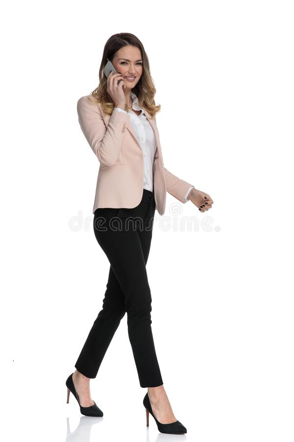 Attractive businesswoman speaking on the phone moves to side royalty free stock images