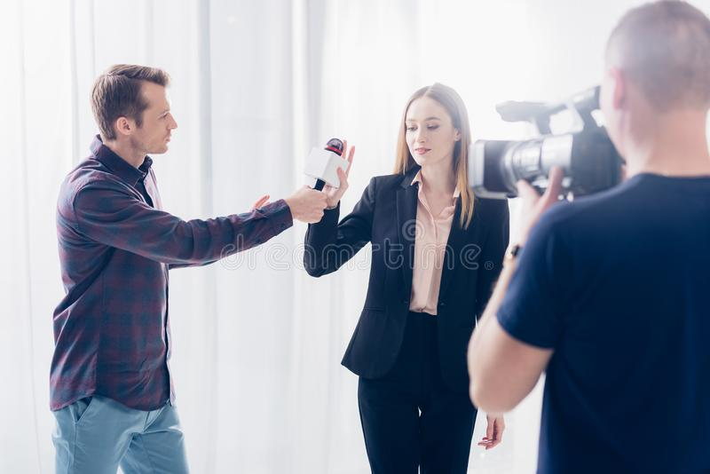 Attractive businesswoman in suit rejecting giving interview to journalist. In office stock photo
