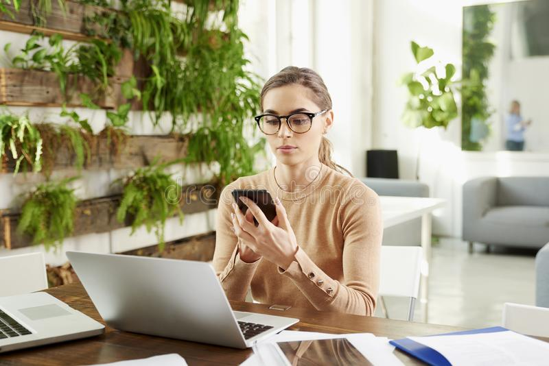 Attractive businesswoman text messaging while sitting at office desk behind her laptop stock images