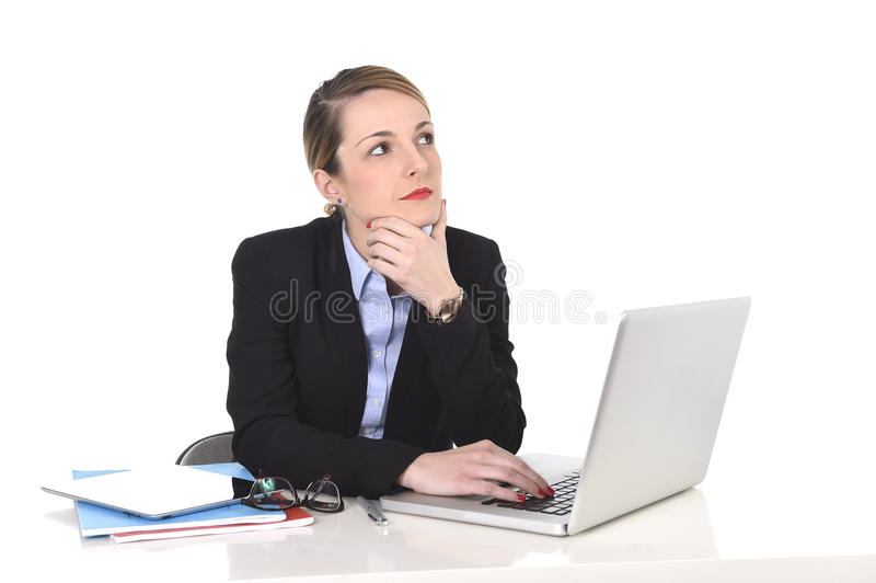 Attractive businesswoman thinking and looking distraught while working on computer. Young attractive blond businesswoman thinking and looking thoughtful, pensive royalty free stock photos