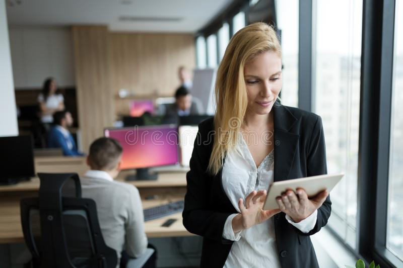 Attractive businesswoman using digital tablet in office stock image