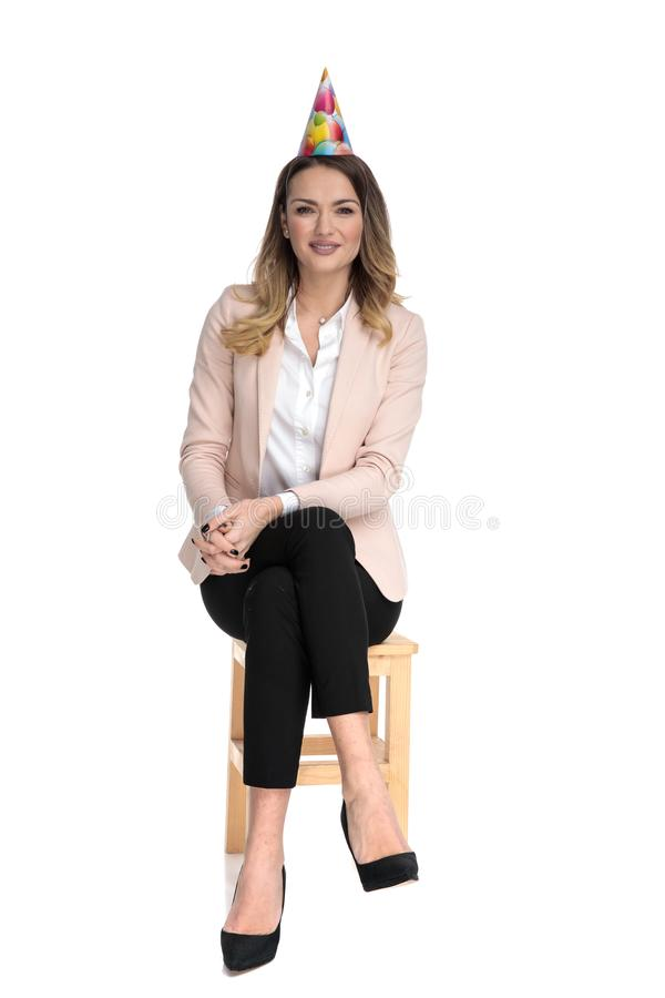 Attractive businesswoman wearing birthday hat and pink suit sits. On wooden chair on white background stock photos