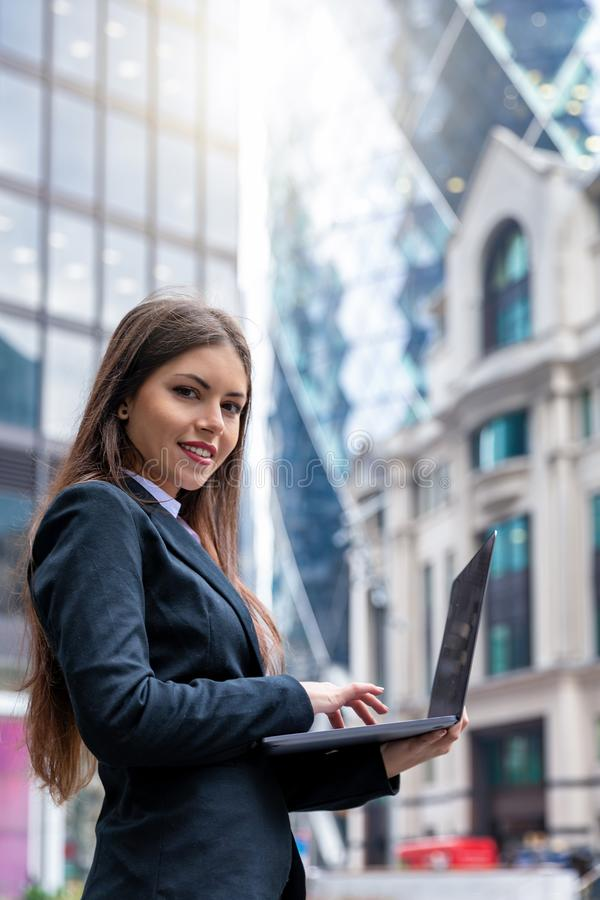 Businesswoman working on laptop outdoors in the City of London. Attractive businesswoman working on laptop outdoors in the City of London and looking into the royalty free stock images