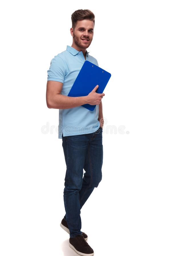 Attractive casual man wearing blue polo short holds blue files. And steps to side with hands in pockets on white background, full body picture royalty free stock photos