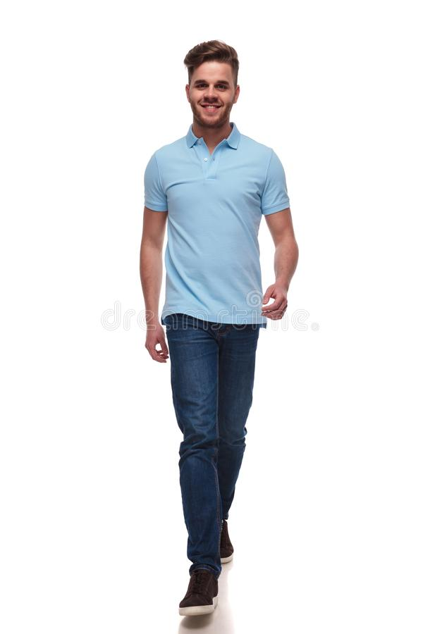Attractive casual man wearing blue polo t-shirt steps forward. On white background, full length picture stock photos
