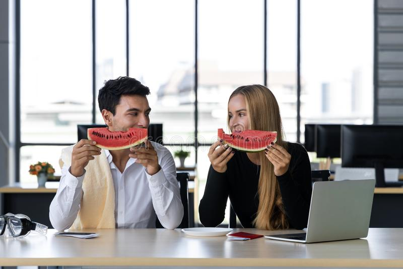 Attractive Caucasian business people eating watermelon in office. Summer vacations concept.  royalty free stock photography
