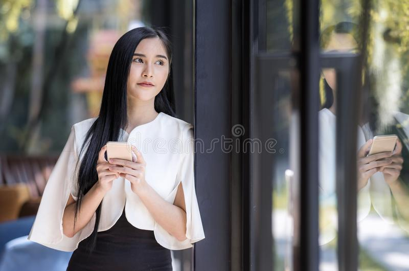 attractive caucasian businesswoman using smartphone near glass w royalty free stock photography
