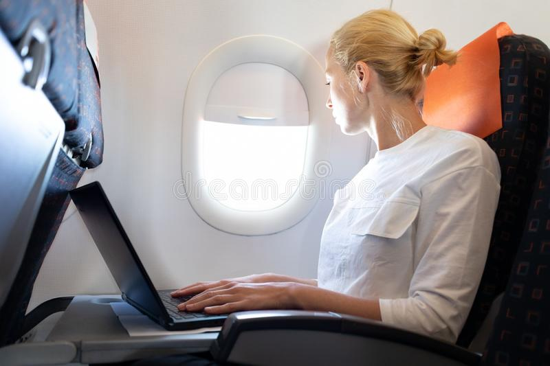 Attractive caucasian female passenger looking through the plain window while working on modern laptop computer using royalty free stock photos