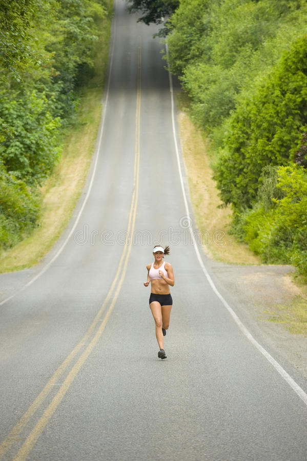 Attractive Caucasian Female Runner on Country Road. Young caucasian female runner on a hilly country road. Zoomed out, vertically framed shot stock image
