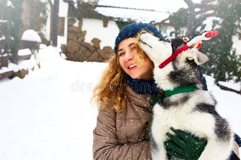 Attractive caucasian woman hugs funny malamute dog wearing santa dear christmas antlers. Curly smiling female having fun royalty free stock images