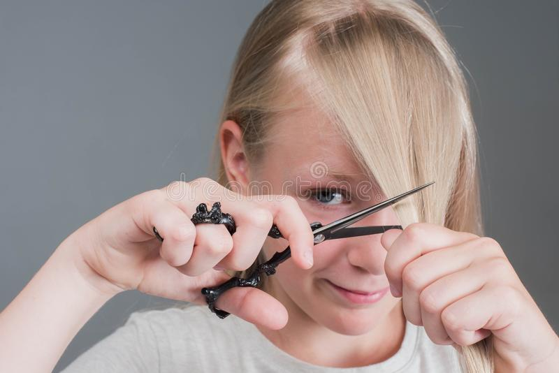 Attractive chaild girl is cutting her long blond natural hair royalty free stock photo